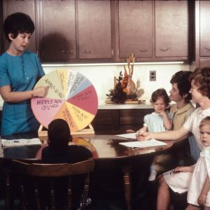 Home Demonstration worker reviews child aging and development with mothers