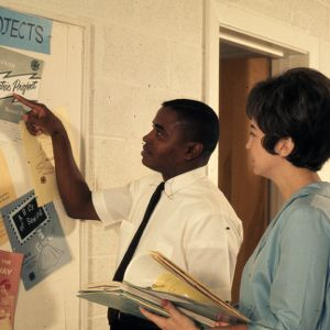 Home Demonstration co-workers review a bulletin board