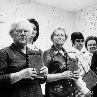 Women holding Macon county recipe books