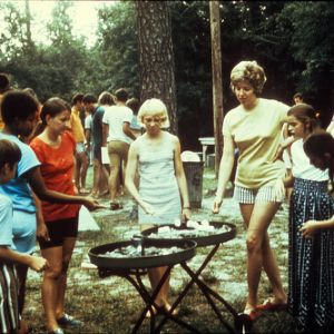 A group of young people roasting marshmallows