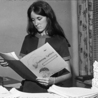 A young woman looking at a beginning families pamphlet