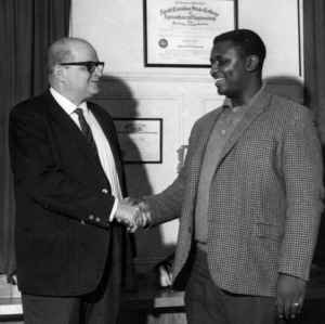 Physical plant's J. McCree Smith and Bobby F. Holloway, shaking hands on Holloway's new appointment