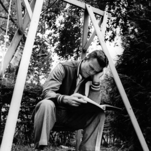 Wolfpack football assistant coach Darrell Royal reading a book on a swing