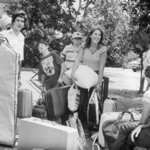 Students outside with their luggage and dorm room items