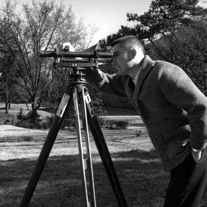 Civil engineering student using surveying equipment