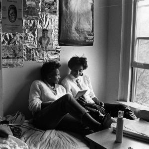 Students looking at album in dorm room