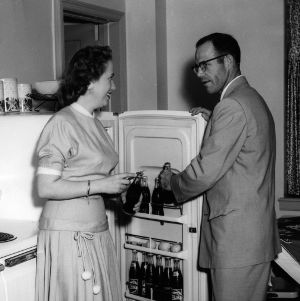 Couple getting Coca-Colas from refrigerator