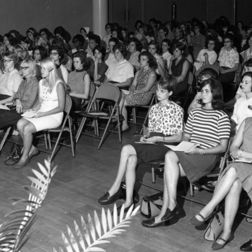Freshman women students at an orientation meeting