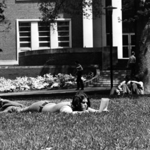 Student laying on grass outside of the D. H. Hill library