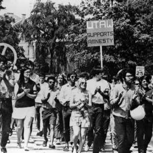 People marching down a street with peace signs