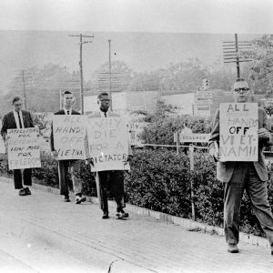 People walking on sidewalk with signs protesting the Vietnam War