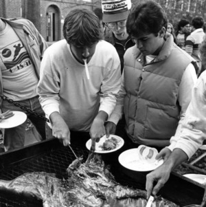 Students cooking a hog