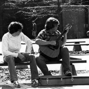 Student playing a guitar on the brickyard