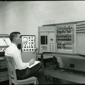 Man sitting in front of a large computing machine