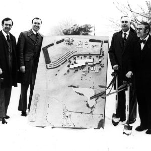 Group at ground breaking ceremony with architect's model