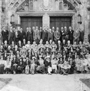 Group of men and women sitting on steps of unidentified building