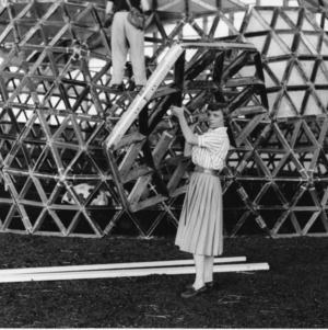 Woman in skirt is holding up hexagonal piece to be placed with other on dome structure