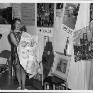Woman holds a quilt in front of a display on Canada