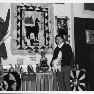 Man stands in front of display and is holding a stuffed llama