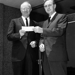 Dr. James H. Brooks receiving check from R. J. Reynolds Tobacco Company's Ivan Neas