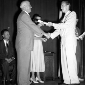 Student receiving diploma from Dean J. H. Lampe