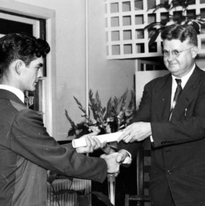 E. W. Ruggles, Director of Extension, giving diploma to graduate