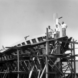Paul B. Mitchell and two Morehead City Technical Institute students observing construction of boat
