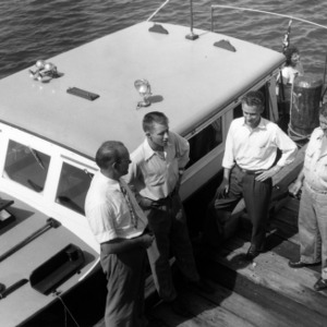 Morehead City Technical Institute's director Paul B. Mitchell and students visiting Reginald Willlis' marine service station