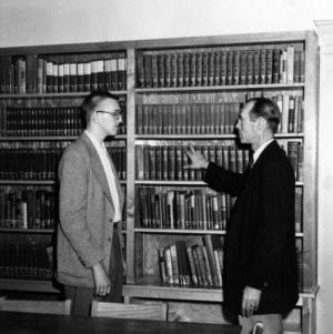 Donald Abernethy, a radio and television technology student, with James I. Mason, director of the Gaston Technical Institute, in the Institute's library
