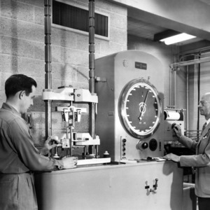 Dr. E. M. Schoenborn and Henry B. Pittman operating electro-mechanical testing machine for Navy plastic research