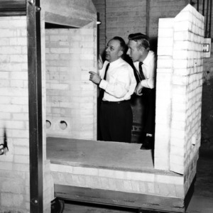 Dr. William C. Bell and Alex Carlyle inspecting shuttle kiln