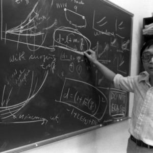 Dr. Chou in front of blackboard