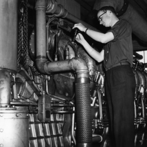 Mechanical Engineering student with diesel engine at the 1956 Engineering Fair