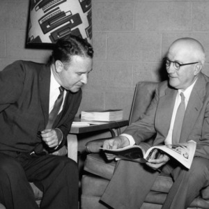 Professor John F. Lee and Dean J. H. Lampe looking at magazine