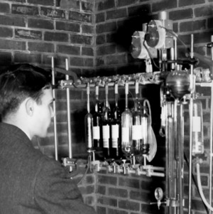 Engineering researcher inspecting a precision gas analyzer