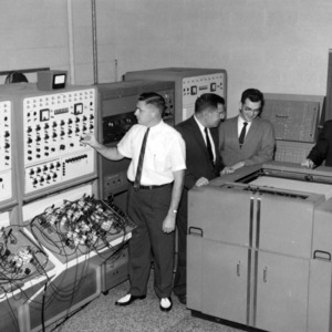 Dr. John W. Cell and graduate research assistants examining data from GEDA Analog Computer