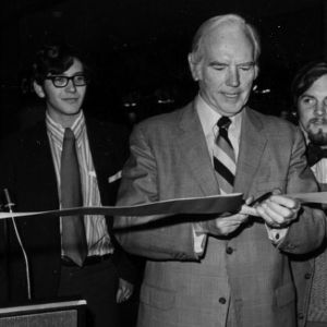 John T. Caldwell cutting ribbon at event