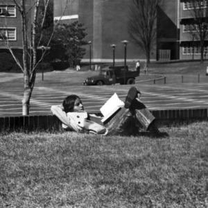 Student reading on Brickyard's grass area