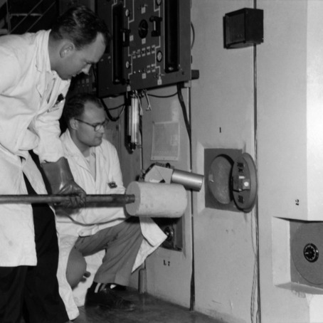 Laboratory Technician Harold Carter and Dr. Wesly Doggett loading a sample into the reactor for irradiation