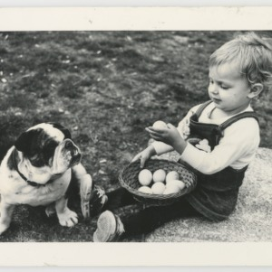 ASPCA Photo: Small child with basket of eggs and bulldog