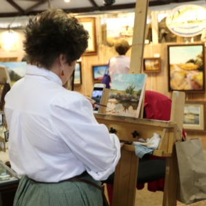 Woman painting art work at North Carolina State Fair, 2018