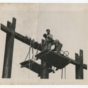 Dorton Arena's workmen atop riveted scaffolding, 1951-1952