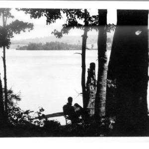 Dr. Carl Schenck sitting on shore of lake