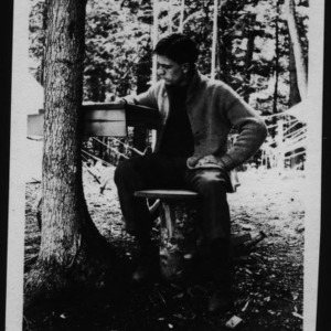 Another view of Ben Alexander posing at a desk underneath a tree