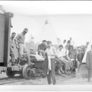 Biltmore Forestry School students sitting on a train flatcar