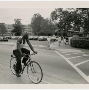 Man rides bike through campus