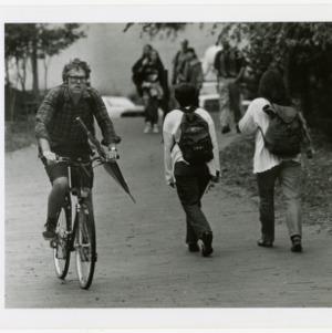 Man carries umbrella while biking through campus