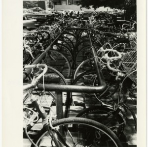 Bicycles and motorcycles in rack outside of Carmichael Gym