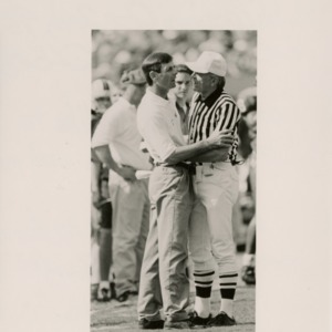 Football coach confers with the referee