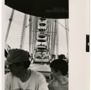 Father and son look over the fair from the ferris wheel